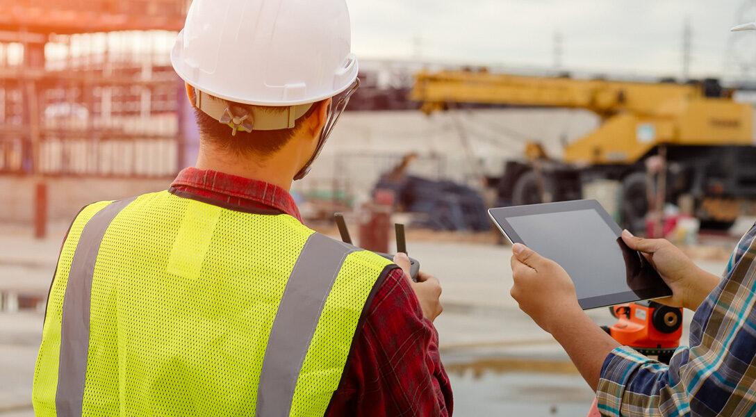 Zdjęcie przedstawia robotników z narzędziami na budowie