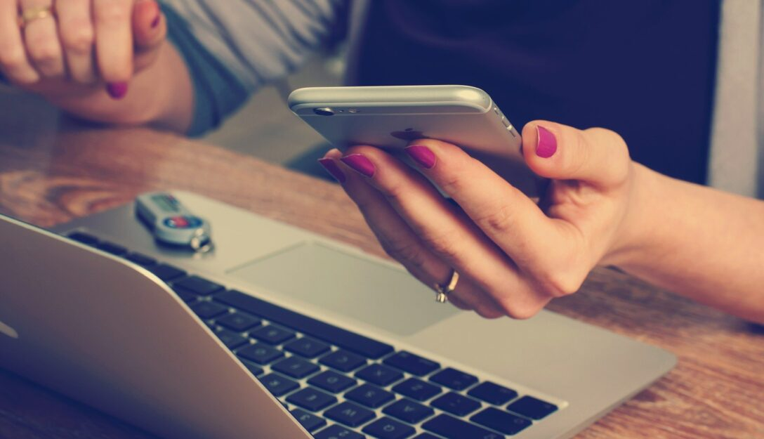 Zdjęcie przedstawia kobietę trzymająca telefon komórkowy