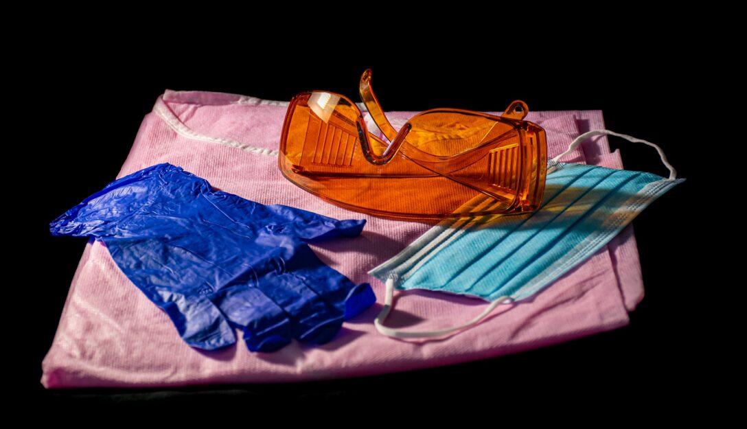 Zdjęcie przedstawia środki ochrony osobistej - maseczki, okulary i rękawiczki